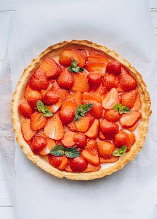 ingredients for strawberry pie, sliced strawberries are laid on top of the pie and smeared on top with lime jelly with fresh green mint leaves