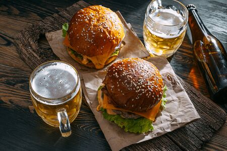 two delicious beef burger on a wooden table near two glass of cold beer Standard-Bild - 147256053