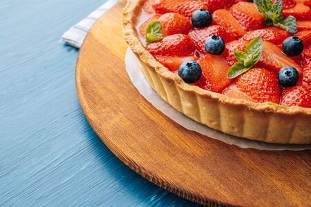 strawberry custard pie with lime zest added to which are sliced strawberries with blueberries and fresh mint leaves and topped with lime jelly on a blue wooden table Standard-Bild - 147256295