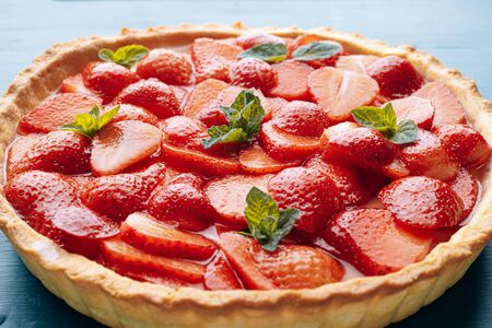 strawberry quiche with lime zest and strawberry slices laid on top and topped with lime jelly on a blue wooden table