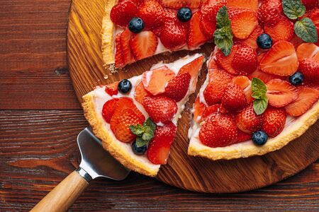 quiche with lime zest on which sliced strawberries with blueberries and fresh mint leaves on a wooden table. one slice is cut out of the pie and it is ready to serve.
