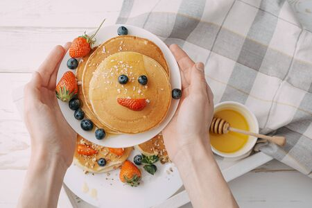 pancake breakfast for children with berries and honey in the shape of a smiling face