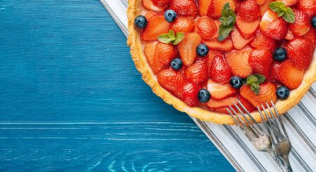 strawberry custard pie with lime zest added to which are sliced strawberries with blueberries and fresh mint leaves and topped with lime jelly on a blue wooden table