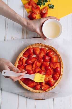 ingredients for strawberry tart, silicone cooking brush sprinkles lime jelly on the surface of the strawberry tart