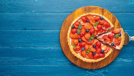 quiche with lime zest and strawberry slices with blueberries and fresh mint leaves on a blue wooden table. one slice is cut out of the pie and it is ready to serve. Фото со стока