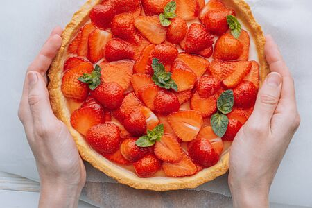 woman cook holding a pie with strawberries custard and mint Фото со стока