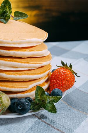 classic homemade pancakes with berries on a white saucer on a dark wooden background in a rustic style. Фото со стока