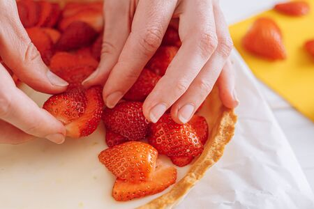 ingredients for strawberry pie, custard cake with lime zest, cutting board with sliced strawberries. female hands lay sliced strawberries on the surface of the cream
