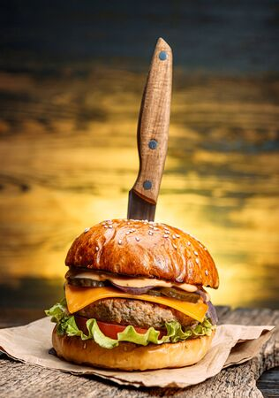 close up tasty beef burger on a wooden table with a knife inserted into it