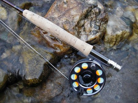 Fishing tackle (fly rod and reel) on stones in a stream