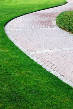 Winding path through a lawn with green grass
