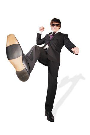 Young man kicking something, isolated on white background