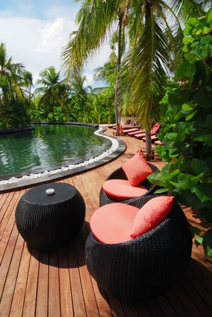 Wicker Table and Chairs with view on Swimming Pool.
