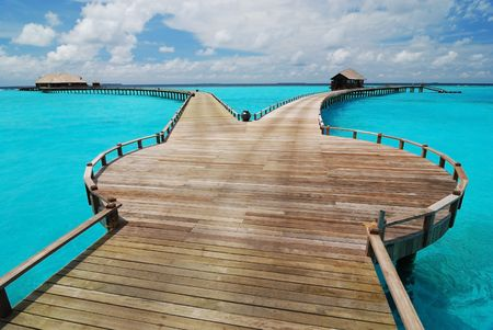Old wooden jetty with two different ways leading out into the Indian Ocean. Stock Photo