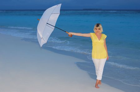 Young woman in yellow dress standing on the beach with white umbrella in the twilight. photo