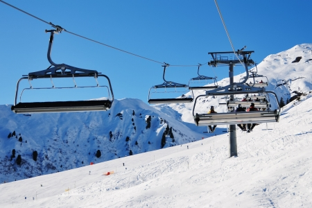 Ski lift chairs. Snowcovered high mountain in Alpes. Mayrhofen, Austria.