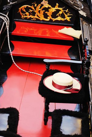 laquered: Traditional venician wooden gondola with glossy black laquered hulls and a gondoliers hat. Stock Photo