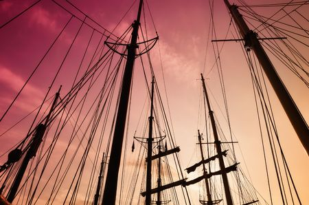 Looking up at silhouette of  ships mast against sky with the red sunsets dying glow (toner).