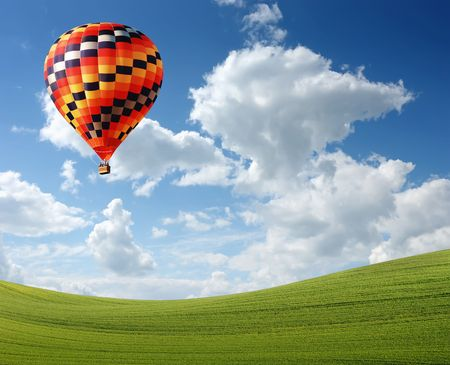 Hot air baloon floating in the sky over land photo