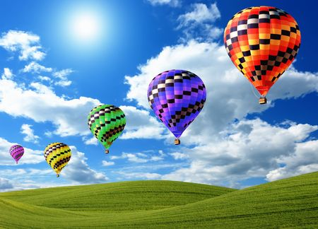Hot air balloons floating in the sky over land Stock Photo