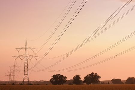 Electric high tension transmission lines head into the horizon at dawn (tinted image). photo