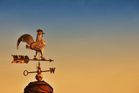 Weather Vane against sunset sky with copy space photo