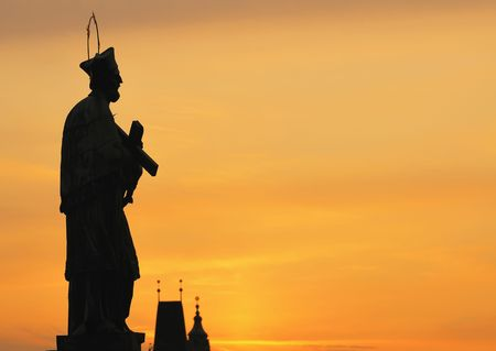 cope: Silhouette statue of St. John of Nepomuk on Charles bridge in Prague against sunset sky with cope space.
