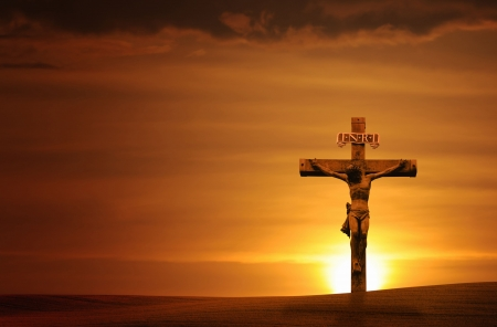 Cross at sunset with a dramatic sky - horizontal.