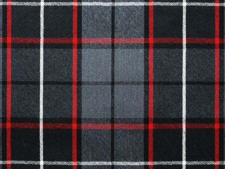 Close up shot of grey wool plaidtartan with red and white stripes.