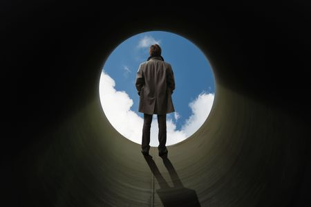 There is no other way out. Man stands silhouetted at the end of tube before a bright sky.