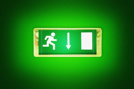 Illuminated of green light emergency exit sign.