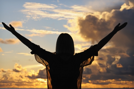 Silhouette of a young woman with outstretched hands against sunset sky