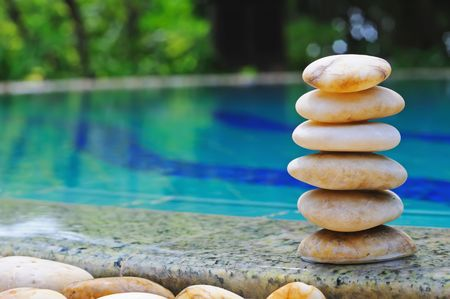 Stack of balanced stones near from swimming pool.