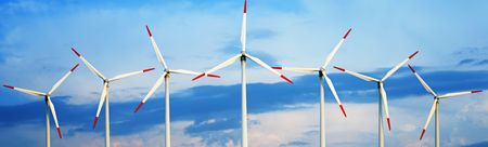Panoramic view of wind turbines against dramatic sky.