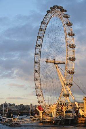 View of Millenium Wheel (London Eye) on Thames river in warm evening sun