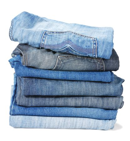 Stacked folded old blue jeans isolated on white background Stock Photo