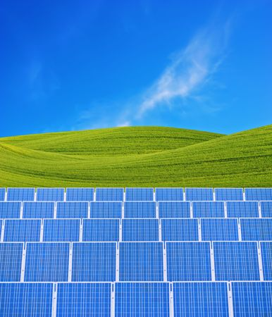 Solar panels and green fields against blue sky.