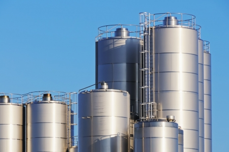 Close up shot of storage tanks of dairy plant against blue sky.