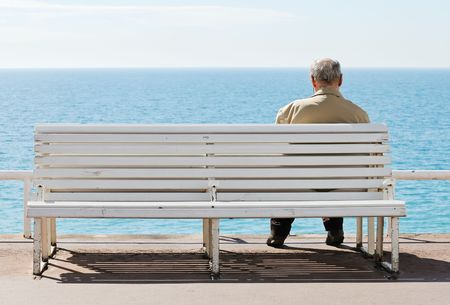 Old men sitting on the bench by the sea.
