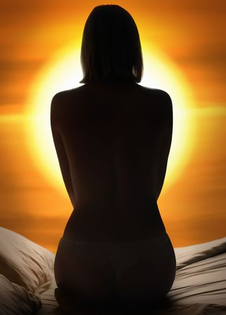 Back view of a woman sitting on a bed against sunset before bedtime