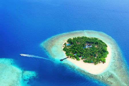 Small tropical island in the ocean, Maldives. Shot was taken from seaplane. Stock Photo
