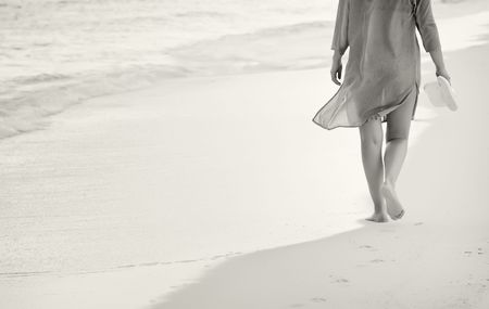 Black and white of young woman walking on the sand Stock Photo