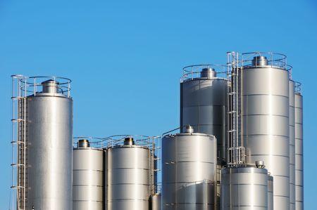 Storage tanks of dairy plant against blue sky. Stock Photo