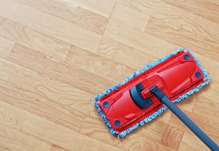 mop: Het reinigen van laminaat. Red mop op hardhoutvloeren. Stockfoto