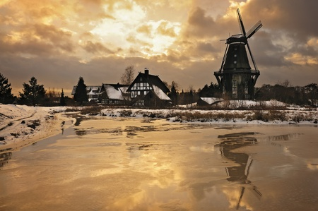 Windmill in winter landscape during sunset with dramatic sky photo