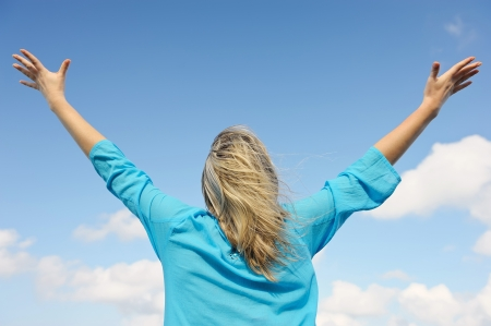 arms  outstretched: Upwards view of young woman enjoying life Stock Photo