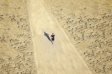 A young man is running in desert on a sunny day