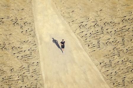 Genç bir adam güneşli bir günde çölde çalışıyor