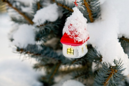 Christmas-tree decoration (glass white house with red roof) on the tree outdoor photo