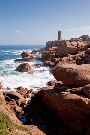 lighthouse in the rocks on Pink Granite Coast in France photo